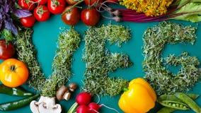 Odgórny widok inskrypcja veg od świeżych mikro rośliien na zielonym tle, zdjęcia stock