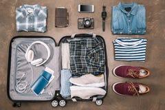 Odgórny widok istotne urlopowe rzeczy w otwartym bagażu z cyfrowymi przyrządami obraz stock