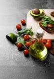 Odgórny widok jarzynowi składniki Butelka oliwa z oliwek, pomidory, sałatka opuszcza i ściska na stołowym tle zdjęcia royalty free