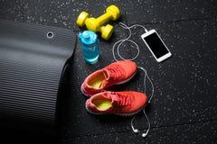 Odgórny widok jaskrawi żółci dumbbells, mata, butelka woda, sportów buty i telefon na czarnym podłogowym tle, zdjęcia royalty free