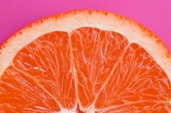 Odgórny widok jeden grapefruitowy plasterek na jaskrawym tle w purpurach barwi Naszły cytrus tekstury wizerunek obrazy royalty free