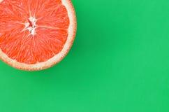 Odgórny widok jeden grapefruitowy plasterek na jaskrawym tle w zielonym kolorze Naszły cytrus tekstury wizerunek obrazy stock