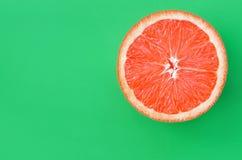 Odgórny widok jeden grapefruitowy plasterek na jaskrawym tle w zielonym kolorze Naszły cytrus tekstury wizerunek zdjęcia stock