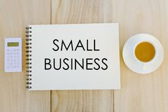 Odgórny widok kalkulator, filiżanka kawy i notatnik pisać z małym biznesem na drewnianym tle, Biznes, finanse i bankowość, fotografia stock