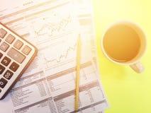 Odgórny widok kalkulatora, ołówka, filiżanki kawy i firmy zbiorczy dane, sporządza mapę na żółtym tle Fotografia Royalty Free
