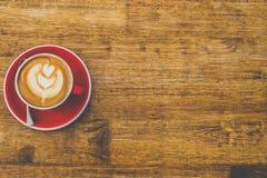 Odgórny widok kawa w czerwonej filiżance na drewnianym stołowym tle zdjęcie stock