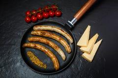 odgórny widok kiełbasy, musztarda, ser i pomidory smażący, obrazy stock