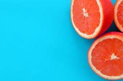 Odgórny widok kilka grapefruitowi plasterki na jaskrawym tle w błękitnym kolorze Naszły cytrus tekstury wizerunek obraz royalty free