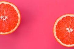 Odgórny widok kilka grapefruitowi plasterki na jaskrawym tle w menchiach barwi Naszły cytrus tekstury wizerunek fotografia stock