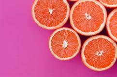Odgórny widok kilka grapefruitowi plasterki na jaskrawym tle w purpurach barwi Naszły cytrus tekstury wizerunek fotografia royalty free