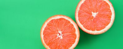 Odgórny widok kilka grapefruitowi plasterki na jaskrawym tle w zielonym kolorze Naszły cytrus tekstury wizerunek zdjęcie stock