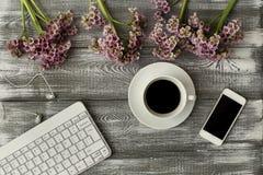 Odgórny widok klawiatura, hełmofony, filiżanka kawy, telefon i purpurowy kwiat na szarym drewnianym stole, Płaski projekt obraz royalty free
