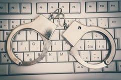 Odgórny widok klawiatura i kajdanki - cyber przestępstwa pojęcie obraz stock