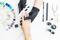 Odgórny widok kobiet ręki w manicure'u procesie na białym stołowym tle z narzędziami dla manicure'u zdjęcia stock