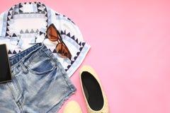 Odgórny widok kobiety Fasonuje eleganckich ubrania podróży akcesoria na kolorowym tle obrazy stock