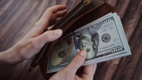 Odgórny widok kobiety liczenie i Bierze out dolary od jej brown rzemiennego portfla Kobieta trzyma kiesy przeciw drewnianemu zbiory wideo