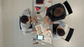 Odgórny widok kolegów projektant wnętrz dyskutuje dane z pustego ekranu nowym nowożytnym komputerowym laptopem i pro cyfrowym obraz stock