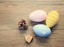 Odgórny widok kolorowi Easter jajka na drewnianym tle Obrazy Stock