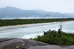 Odgórny widok krajobraz z ludźmi chodzi wśród piaska i fal morze i góry w tle fotografia stock