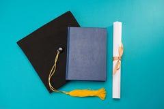 Odgórny widok książka, skalowania mortarboard i dyplom na błękicie, obrazy royalty free
