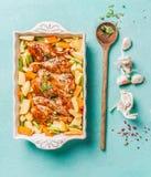 Odgórny widok kurczaków drumsticks z warzywami w wypiekowej potrawce na bławym tle z kulinarną łyżką i podprawą zdjęcie stock