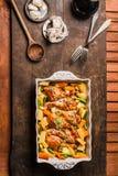 Odgórny widok kurczaków drumsticks z warzywami w wypiekowej potrawce na nieociosanym drewnianym tle fotografia stock