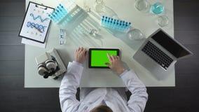 Odgórny widok laboranckiego pracownika scrolling pastylka z zieleń ekranem, nowożytny lab zbiory wideo