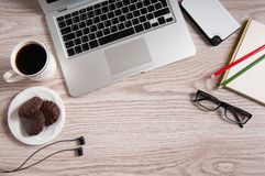 Odgórny widok laptop i notepad z szkłami i hełmofonami na nieociosanym drewnianym desktop i filiżance kawy Zdjęcie Royalty Free