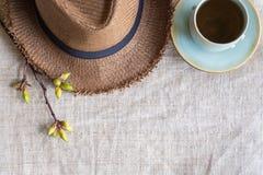 Odgórny widok lata brązu Panama słomiany kapelusz z filiżanką herbata i fl Zdjęcia Stock