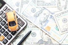 Odgórny widok lub mieszkanie nieatutowi miniaturowy samochodu model, kalkulator i pióro na Amerykańskich dolarach, spieniężamy pi zdjęcia royalty free