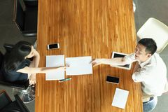 Odgórny widok ludzie biznesu siedzi za spotkania biurkiem, wręcza out dokumenty Zdjęcie Stock