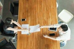 Odgórny widok ludzie biznesu siedzi za spotkania biurkiem, wręcza out dokumenty Zdjęcia Royalty Free