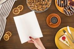 odgórny widok ludzkiego ręki mienia pusty menu i różnorodni wyśmienicie ciastka obraz stock