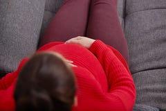 Odgórny widok młoda ciężarna kobieta w czerwonej bluzie i leggings, utrzymuje ręki na brzuszku, cieszy się dobrą domową atmosferę obraz royalty free