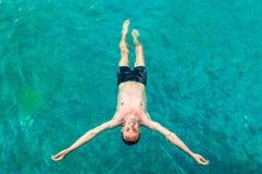 Odgórny widok młody człowiek unosi się w pływackim basenie z otwartymi rękami fotografia royalty free