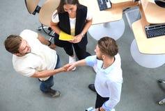 Odgórny widok młodzi partnery biznesowi trząść ręki nad transakcją przy biurem Ostrość na ręki potrząśnięciu fotografia royalty free