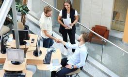 Odgórny widok młodzi partnery biznesowi trząść ręki nad transakcją przy biurem Ostrość na ręki potrząśnięciu obraz royalty free