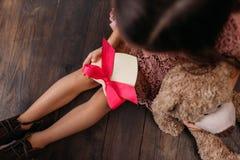 odgórny widok małego dziecka mienia giftbox w kształcie serce podczas gdy siedzący zdjęcia royalty free