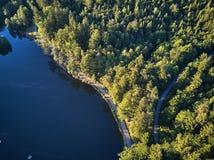 Odgórny widok mały jezioro wokoło zieleni drzewa i z małą ulicą lub ścieżką Zdjęcia Stock