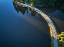 Odgórny widok mały jezioro wokoło zieleni drzewa i z małą ulicą lub ścieżką Zdjęcie Royalty Free