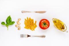Odgórny widok makaronu cutlery nad białym tłem i składniki surowy fusilli, świeży basil, czosnków cloves, oliwa z oliwek i dojrza Obraz Stock