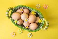 Odgórny widok, mieszkanie nieatutowy wielkanoc życie wciąż Nieociosani brązów jajka w łozinowym koszu wykładali z w kratkę tkanin fotografia stock