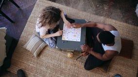 Odgórny widok multiracial pary obsiadanie na podłoga i bawić się grą planszowa Kobieta rzuca kostka do gry, wp8lywy karta Mężczyz Obraz Royalty Free