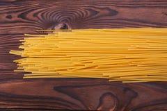 Odgórny widok na żółtym makaronie Uncooked makaron na drewnianym tle Smakowici jarscy kluski Domowej roboty obiadowy pojęcie Obraz Stock