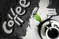 Odgórny widok na filiżance gorąca czarna kawa z zielenią i teksta słowa ręka pisać w angielskiego ` kawowym ` opuszcza w mlejącej Zdjęcia Stock