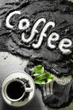 Odgórny widok na filiżance gorąca czarna kawa z zielenią i teksta słowa ręka pisać w angielskiego ` kawowym ` opuszcza w mlejącej Obrazy Stock