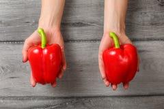 Odgórny widok na kobiecie wręcza mieniu dwa czerwonego dzwonkowego pieprzu nad szarość w Obrazy Stock