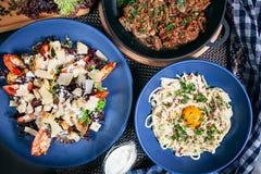 Odgórny widok na słuzyć jedzenie stole Caesar sałatka z garnelami, mięsna niecka, carbonara na błękita talerzu zdjęcia royalty free