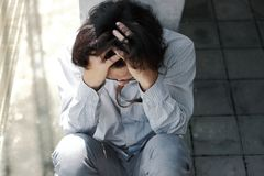 Odgórny widok niespokojny sfrustowany młody Azjatycki biznesowego mężczyzna obsiadanie i wzruszający czoło z rękami zdjęcie royalty free