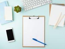 Odgórny widok nowożytny błękitny biurowy desktop z pustym notepad, komputer, smartphone Egzamin próbny up, opróżnia przestrzeń obraz royalty free